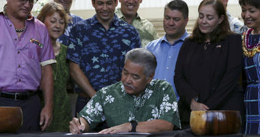 Hawaii Gov. David Ige signs legislation banning the sale of sunscreens containing two chemicals believed to harm coral reefs Tuesday, July 3, 2018, in Honolulu. The law makes Hawaii the first U.S. state to enact a ban on oxybenzone and octinoxate.