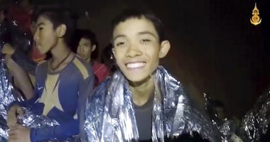 Thai boys smile as Thai Navy SEAL medic help injured children inside a cave in Mae Sai, northern Thailand. The Thai soccer teammates stranded more than a week in the partly flooded cave said they were healthy on a video released Wednesday.