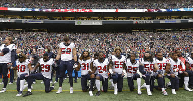 In this Oct. 29, 2017, file photo, Houston Texans players kneel and stand during the singing of the national anthem before an NFL football game against the Seattle Seahawks, in Seattle.