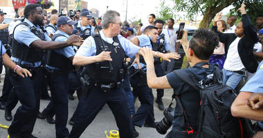 Members of the Chicago police department scuffle with an angry crowd at the scene of a police involved shooting in Chicago, on Saturday, July 14, 2018.