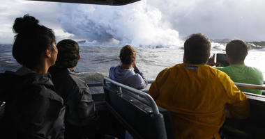 In this May 20, 2018 file photo, people watch a plume of steam as lava enters the ocean near Pahoa, Hawaii. Officials say an explosion sent lava flying through the roof of a tour boat off the Big Island, Monday, July 16, 2018, injuring at least 13 people.