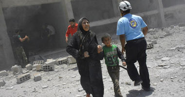 In this June 14, 2017, file photo, provided by the Syrian Civil Defense group known as the White Helmets, shows civilians rushing out of the damaged buildings after airstrikes hit a school housing a number of displaced people.