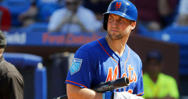 New York Mets' Tim Tebow walks back to the dugout after striking out during the second inning of an exhibition spring training baseball game against the Washington Nationals.