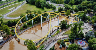 In this July 23, 2018, aerial image in Hershey, Pa., muddy brown floodwaters in Spring Creek flow beneath the Skyrush roller coaster, in yellow, and past the Comet roller coaster, in white, at Hersheypark.