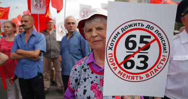 "An elderly woman holds a poster reads ""Want to Retire, it's time to change the authority!"" during a rally protesting retirement age hikes in Moscow, Russia, Saturday, July 28, 2018."