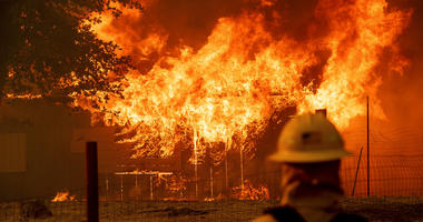 A firefighter monitors a burning outbuilding to ensure flames don't spread as the River Fire burns in Lakeport, Calif., on Monday, July 30, 2018.