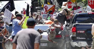 In this Aug. 12, 2017, file photo, people fly into the air as a vehicle drives into a group of protesters demonstrating against a white nationalist rally in Charlottesville, Va.
