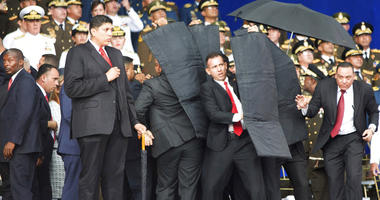 In this photo released by China's Xinhua News Agency, security personnel surround Venezuela's President Nicolas Maduro during an incident as he was giving a speech in Caracas, Venezuela, Saturday, Aug. 4, 2018.