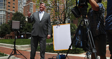 Attorney Kevin Downing, left, gestures to the rest of the defense team for Paul Manafort, as the team leaves federal court for a lunch break during the trial of the former Trump campaign chairman, in Alexandria, Va., Thursday, Aug. 9, 2018.