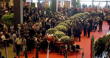 People gather for a funeral service for some of the victims of a collapsed highway bridge, in Genoa's exhibition center Fiera di Genova, Italy, Saturday, Aug. 18, 2018.