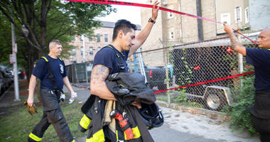 Chicago firefighters walk under tape at the scene of a fire that killed several people including multiple children Sunday, Aug. 26, 2018, in Chicago.