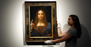 """In this Oct. 24, 2017 file photo, an employee poses with Leonardo da Vinci's """"Salvator Mundi"""" on display at Christie's auction rooms in London."""