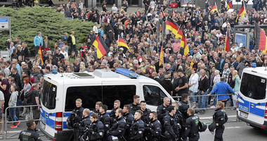 People are watched by police as they attend a demonstration in eastern Germany, Sept. 7, 2018, after several nationalist groups called for marches protesting the killing of a German man two weeks ago, allegedly by migrants from Syria and Iraq.
