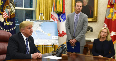 President Donald Trump, left, listens to a reporters question as FEMA Administrator Brock Long, center, and Homeland Security Secretary Kirstjen Nielsen, right, listen during a briefing on Hurricane Florence in the Oval Office of the White House.