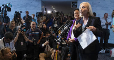 Sen. Kirsten Gillibrand, D-N.Y., joined at rear by Sen. Mazie Hirono, D-Hawaii, holds a letter of support from alumnae from the Holton-Arms School, the Maryland all-girls school that Christine Blasey Ford attended in the early 1980s.