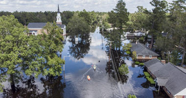 Kayaks are paddled up Long Avenue past flooded sections of the Sherwood Drive community of Conway, S.C., Sunday, Sept. 23, 2018 as homes were submerged deeper than ever in flood waters that have already set historic records.