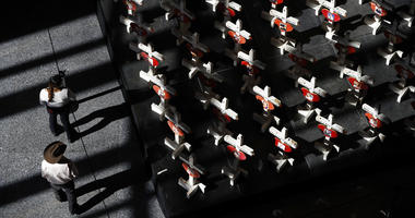 In this Sept. 25, 2018, photo, people look at a display of wooden crosses and a Star of David on display at the Clark County Government Center in Las Vegas.
