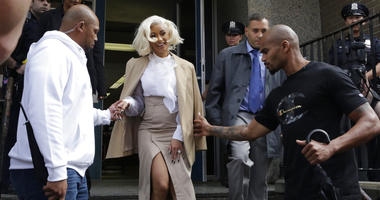 Rapper Cardi B is assisted by security guards as she leaves a police precinct, Monday, Oct. 1, 2018, in the Queens borough of New York.