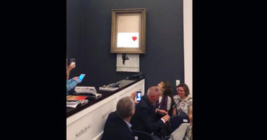 """In this file image taken from video on Friday, Oct. 5, 2018, people watch as the spray-painted canvas """"Girl with Balloon"""" by artist Banksy is shredded at Sotheby's, in London."""