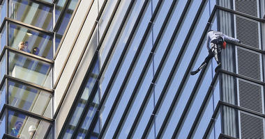 People watch from inside the building as urban climber dubbed the French Spiderman, Alain Robert scales the outside of Heron Tower building in the City of London, Thursday, Oct. 25, 2018.