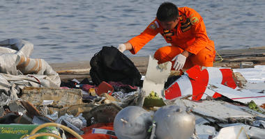 A member of Indonesian Search and Rescue Agency (BASARNAS) inspects debris believed to be from Lion Air passenger jet that crashed off Java Island at Tanjung Priok Port in Jakarta, Indonesia Monday, Oct. 29, 2018.