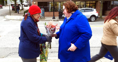 Kristin Wessell, right, hands a bouquet of flowers to Marianne Novy on Murray Avenue in the Squirrel Hill neighborhood of Pittsburgh, Monday, Oct. 29, 2018.