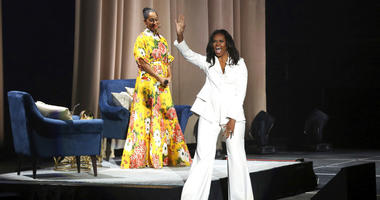 "Former first lady Michelle Obama greets the audience as Tracee Ellis Ross watches at the ""Becoming: An Intimate Conversation with Michelle Obama"" event at the Forum on Thursday, Nov. 15, 2018, in Inglewood, Calif."
