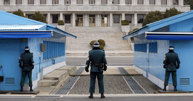 In this March 12, 2014, file photo, a North Korean soldier, center top, looks at the southern side as three South Korean soldiers guard at the border village of Panmunjom, which has separated the two Koreas since the Korean War, in Paju, South Korea.