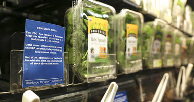 FILE - In this Nov. 20, 2018, file photo Lisa Dennis selects a head of green lettuce from the vegetable shelves at the East End Food Co-op Federal Credit Union in Pittsburgh.