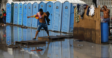 A migrant, part of the migrant caravan, try to cross a flooded area after bathing at a sports complex where more than 5,000 Central American migrants are sheltering in Tijuana, Mexico, Wednesday, Nov. 28, 2018.