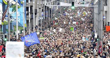 Demonstrators hold signs and wave flags as they march in the main EU quarter during a 'Claim the Climate' march in Brussels, Sunday, Dec. 2, 2018.