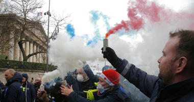 Ambulance workers hold flares outside the National Assembly in Paris, Monday, Dec. 3, 2018.