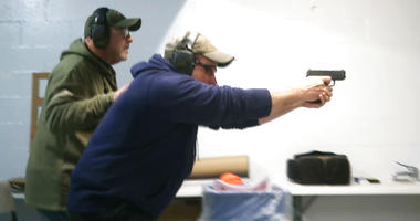 In this photo taken from a video shot on Nov. 28, 2018, Mike Carnevale places his hand on the back of Mark Hennesey while instructing him at the American Tactical Systems' indoor range in Green Island, New York.