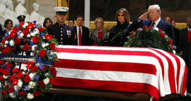 President Donald Trump and first lady Melania Trump pay their respects to former President George H.W. Bush, as he lies in state in the Rotunda of the U.S. Capitol, Monday, Dec. 3, 2018, in Washington.