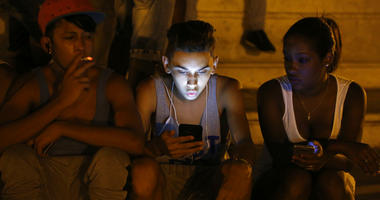 FILE - In this July 1, 2015 file photo, youths use a password protected wifi network coming from a five star hotel to surf the Internet on their smart phones in downtown Havana, Cuba.