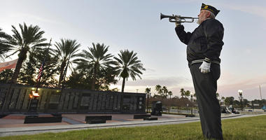 Beaches Honor Guard bugler John Poe plays Taps in honor of former President George H.W. Bush on the day of his funeral Thursday, Dec. 6, 2018 at the Veteran's Memorial Wall at TIAA Bank Field in Jacksonville, Fla.
