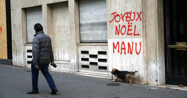 """A man walks his dog past a tag reading """"Happy Christmas Manu,"""" referring to French President Emmanuel Macron."""