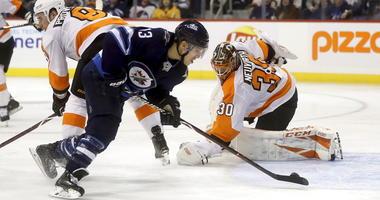 Winnipeg Jets' Brandon Tanev (13) scores against Philadelphia Flyers' goaltender Michal Neuvirth (30) after getting past Flyers' Ivan Provorov (9) during second-period NHL hockey game action in Winnipeg, Manitoba, Sunday, Dec. 9, 2018.