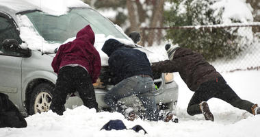 Good samaritans help a driver who is lodged in the snow Sunday, Dec. 9, 2018, along South Hawthorne Road in Winston-Salem, N.C.