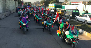Iraqi security forces parade on motorcycles national flags marking the year anniversary of the defeat of the Islamic State group in Iraq in Tahrir Square, in central Baghdad, Monday, Dec. 10, 2018.