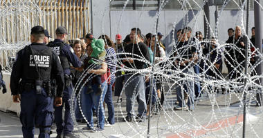 FILE - In this Nov. 19, 2018, file photo, people line up to cross into the United States from Tijuana, Mexico, seen through barriers topped with concertina wire at the San Ysidro port of entry in San Diego.
