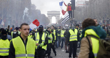 In this Nov. 24, 2018, file photo, demonstrators march on the famed Champs-Elysees avenue in Paris, France, as they protest the rising of the fuel prices.