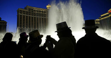 FILE - In this Dec. 31, 2015, file photo, people watch the fountains at the Bellagio while wearing paper hats to celebrate New Years Eve in Las Vegas.