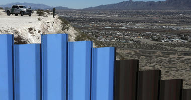 FILE - In this Jan. 25, 2017, file photo, an agent from the border patrol, observes near the Mexico-US border fence, on the Mexican side, separating the towns of Anapra, Mexico and Sunland Park, N.M.