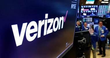 FILE- This April 23, 2018, file photo shows the logo for Verizon above a trading post on the floor of the New York Stock Exchange.