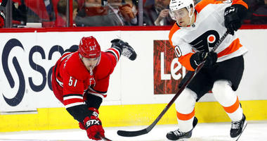Carolina Hurricanes' Trevor van Riemsdyk (57) dives to tip the puck away from Philadelphia Flyers' Jordan Weal (40) during the second period of an NHL hockey game, Monday, Dec. 31, 2018, in Raleigh, N.C.