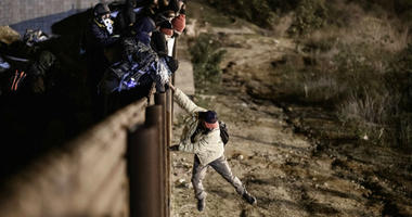 A migrant jumps the border fence to get into the U.S. side to San Diego, Calif., from Tijuana, Mexico, Tuesday, Jan. 1, 2019.