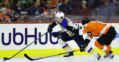 Philadelphia Flyers' James van Riemsdyk, center, is shoved into an official by St. Louis Blues' Robert Bortuzzo, right, during the first period of an NHL hockey game, Monday, Jan. 7, 2019, in Philadelphia.