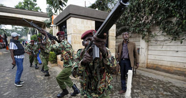 Kenyan security forces aim their weapons up at buildings as they run through a hotel complex in Nairobi, Kenya Tuesday, Jan. 15, 2019.
