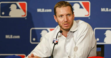 FILE - In this Dec. 9, 2013, file photo, two-time Cy Young Award winner Roy Halladay answers questions after announcing his retirement after 16 seasons in the major leagues with Toronto and Philadelphia at the MLB winter meetings in Lake Buena Vista, Fla.
